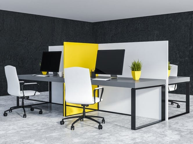 White and yellow office cubicles with gray computer tables and white chairs standing in room with black walls and concrete floor. 3d rendering
